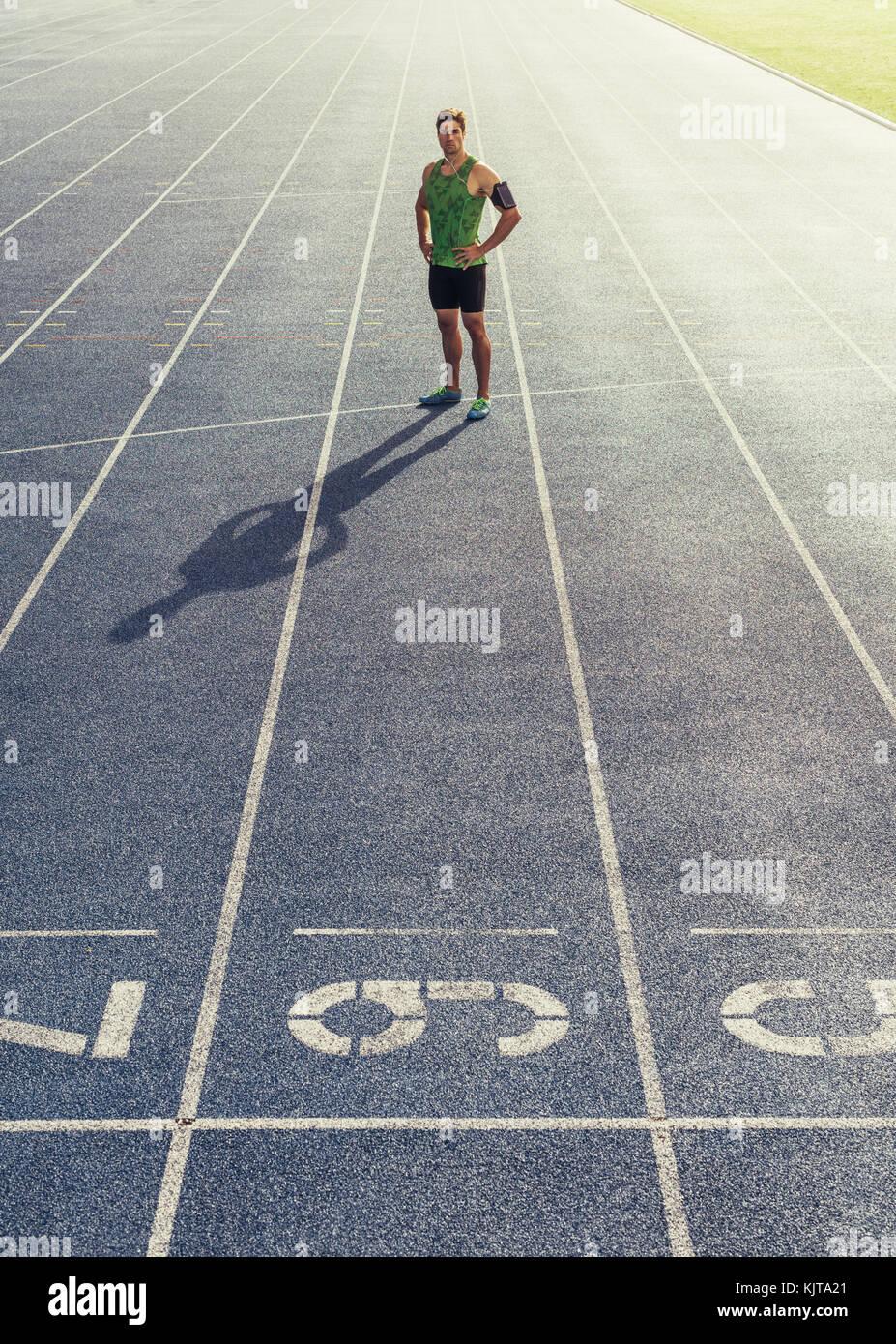 Runner permanente sulla via di corsa con le mani piegate. Atleta che indossa auricolari con telefono mobile fissato Immagini Stock