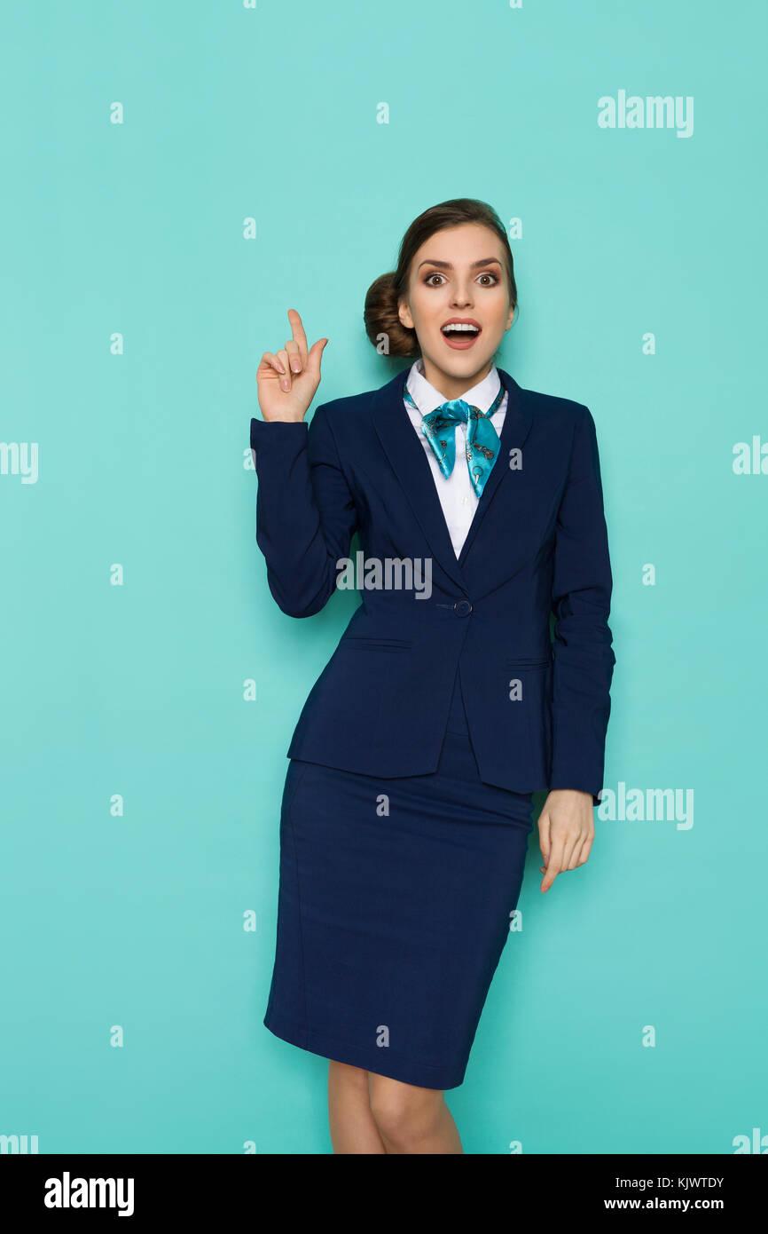 Hostess eccitato in blu abbigliamento formale è rivolta verso l'alto e guardando la fotocamera. tre quarti Immagini Stock