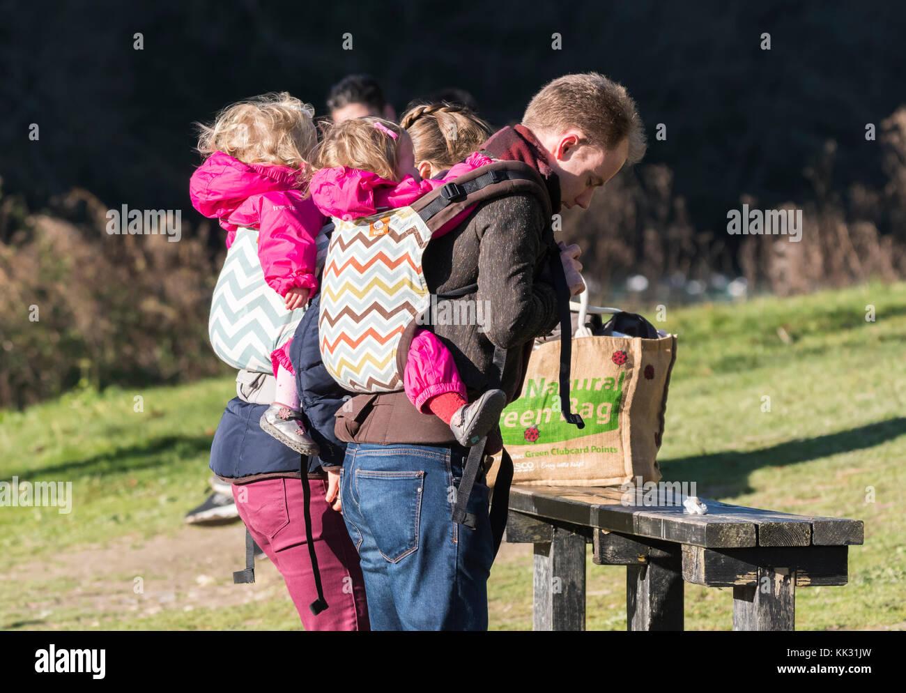 Una coppia con bimbo indietro portanti con i bambini sulle loro spalle. Immagini Stock