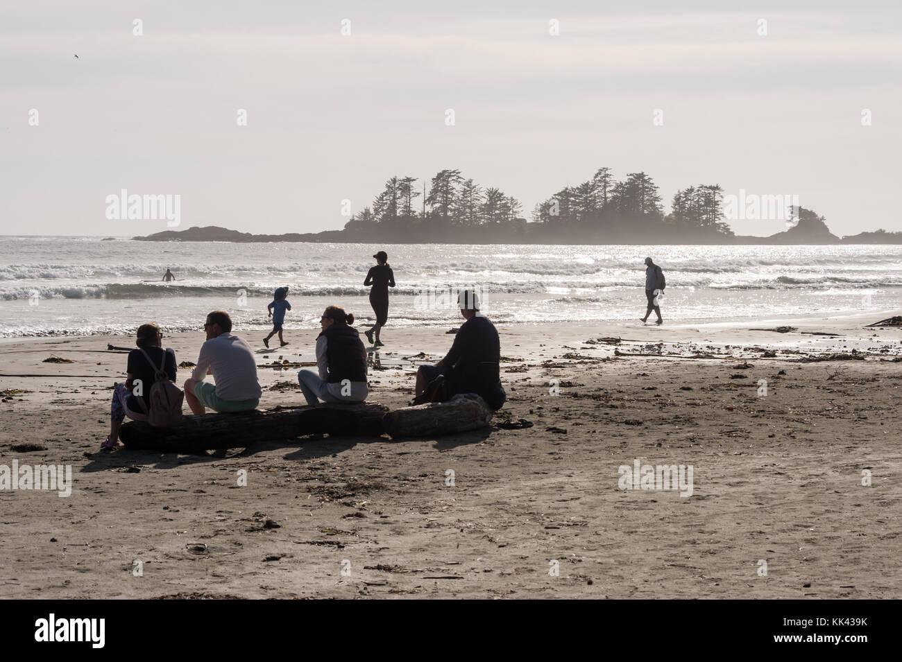 Chesterman beach vicino a Tofino, BC, Canada (settembre 2017) - famiglia seduta sul registro di legno. Immagini Stock