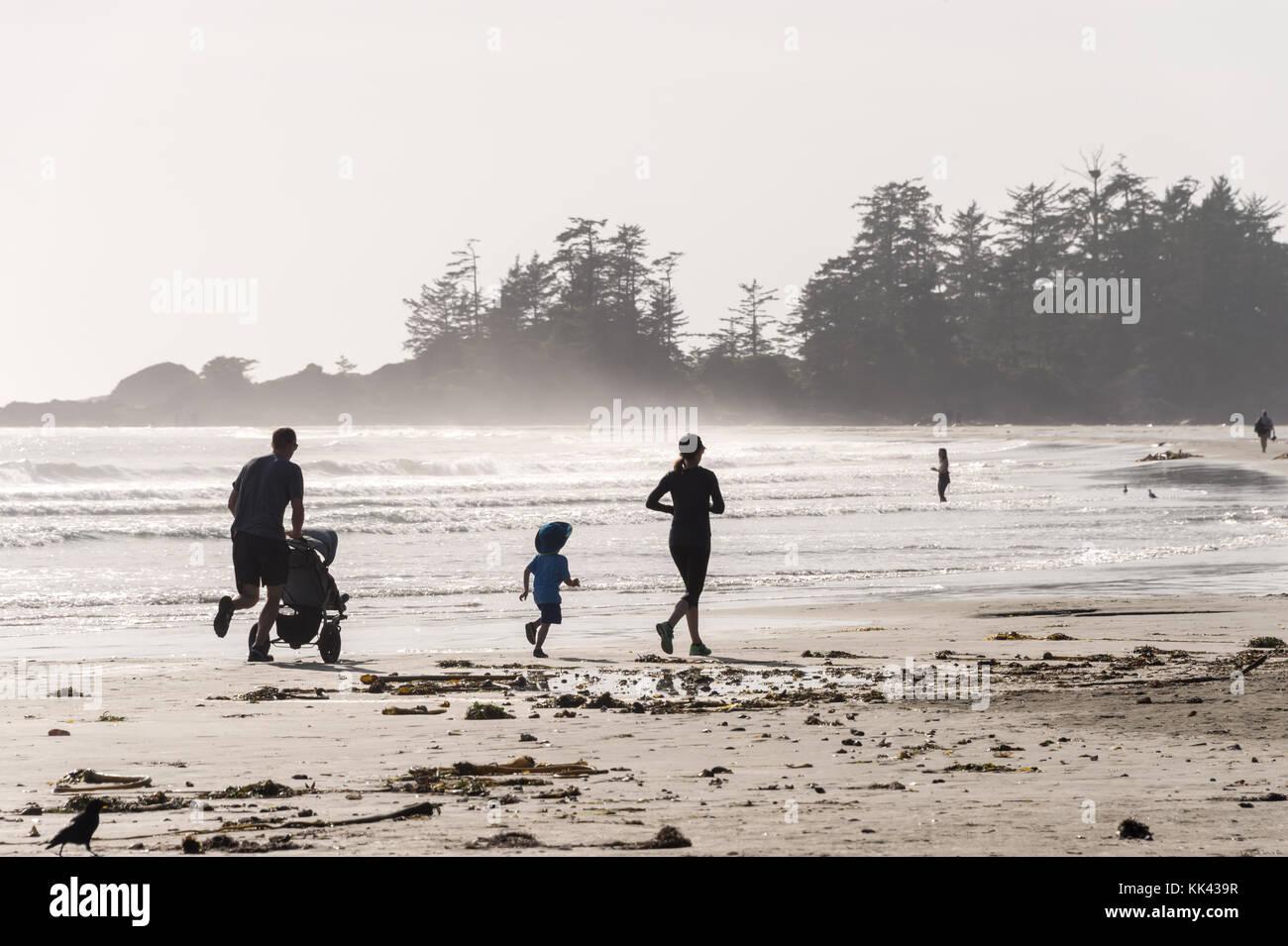 Chesterman beach vicino a Tofino, BC, Canada (settembre 2017) - Famiglia in esecuzione sulla sabbia. Immagini Stock