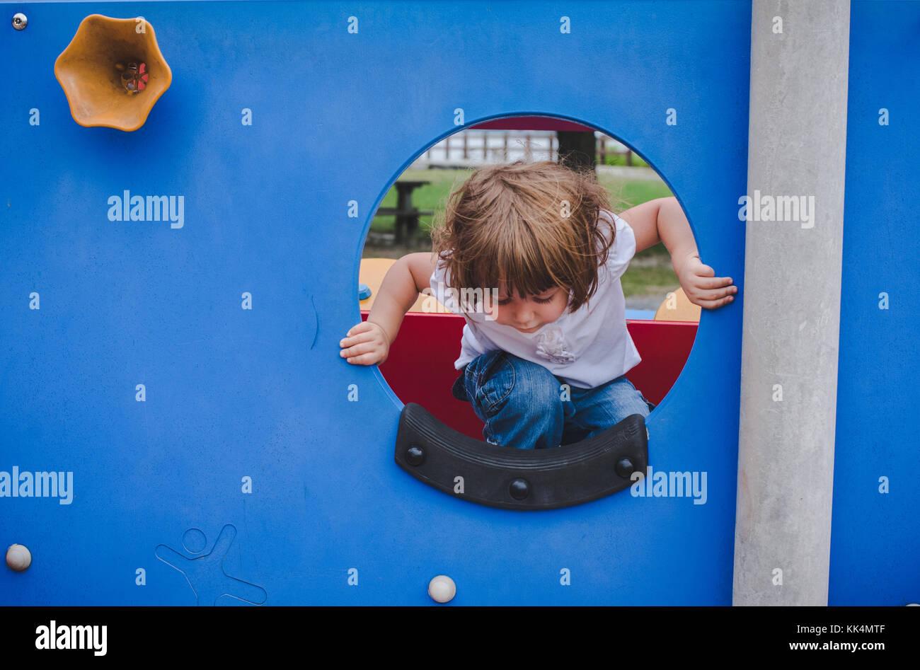 Una bambina si arrampica sulle attrezzature per parchi giochi sul giorno di estate Immagini Stock