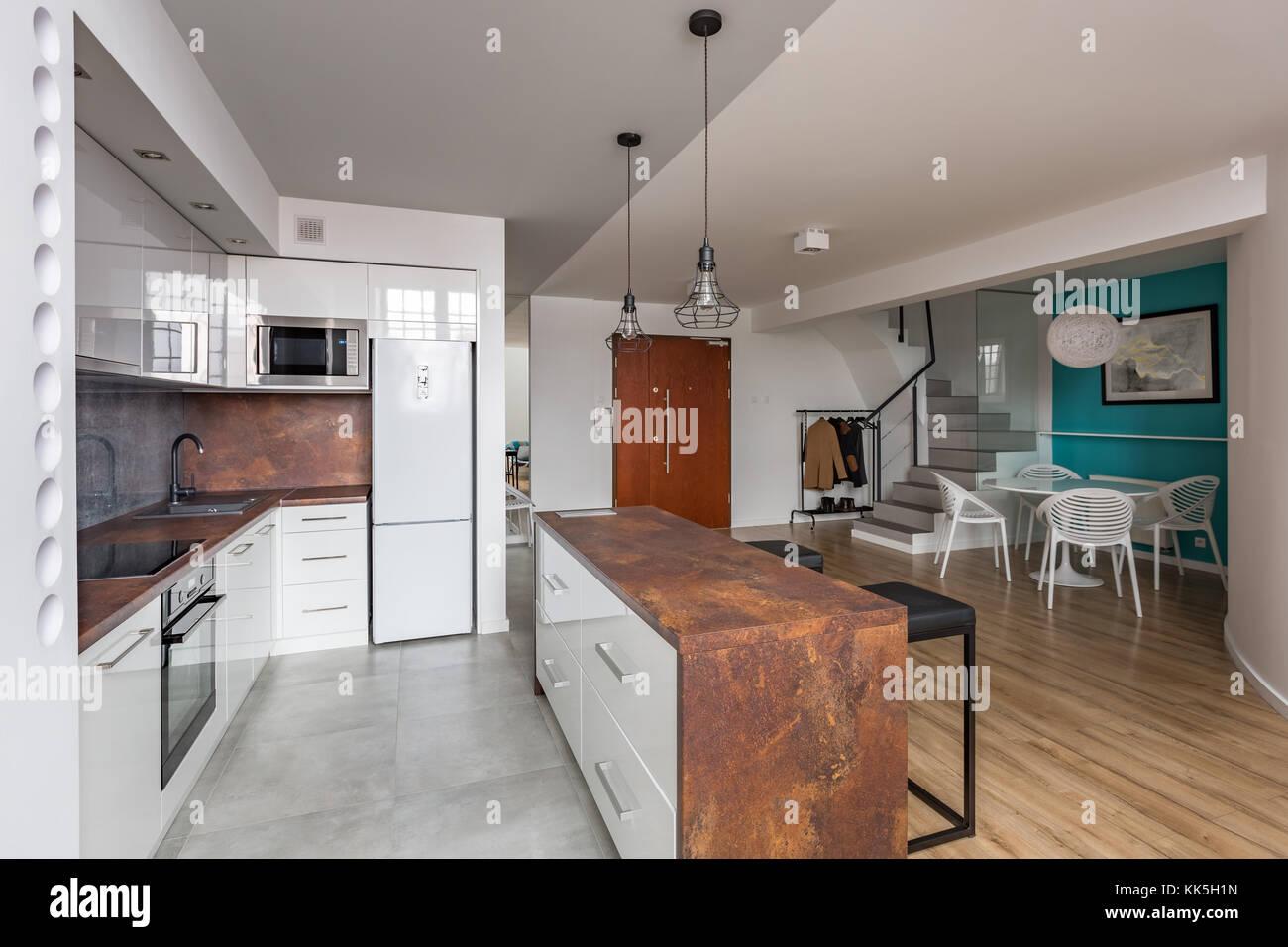 Cucina moderna con cucina aperta con isola, tavolo da pranzo e delle ...