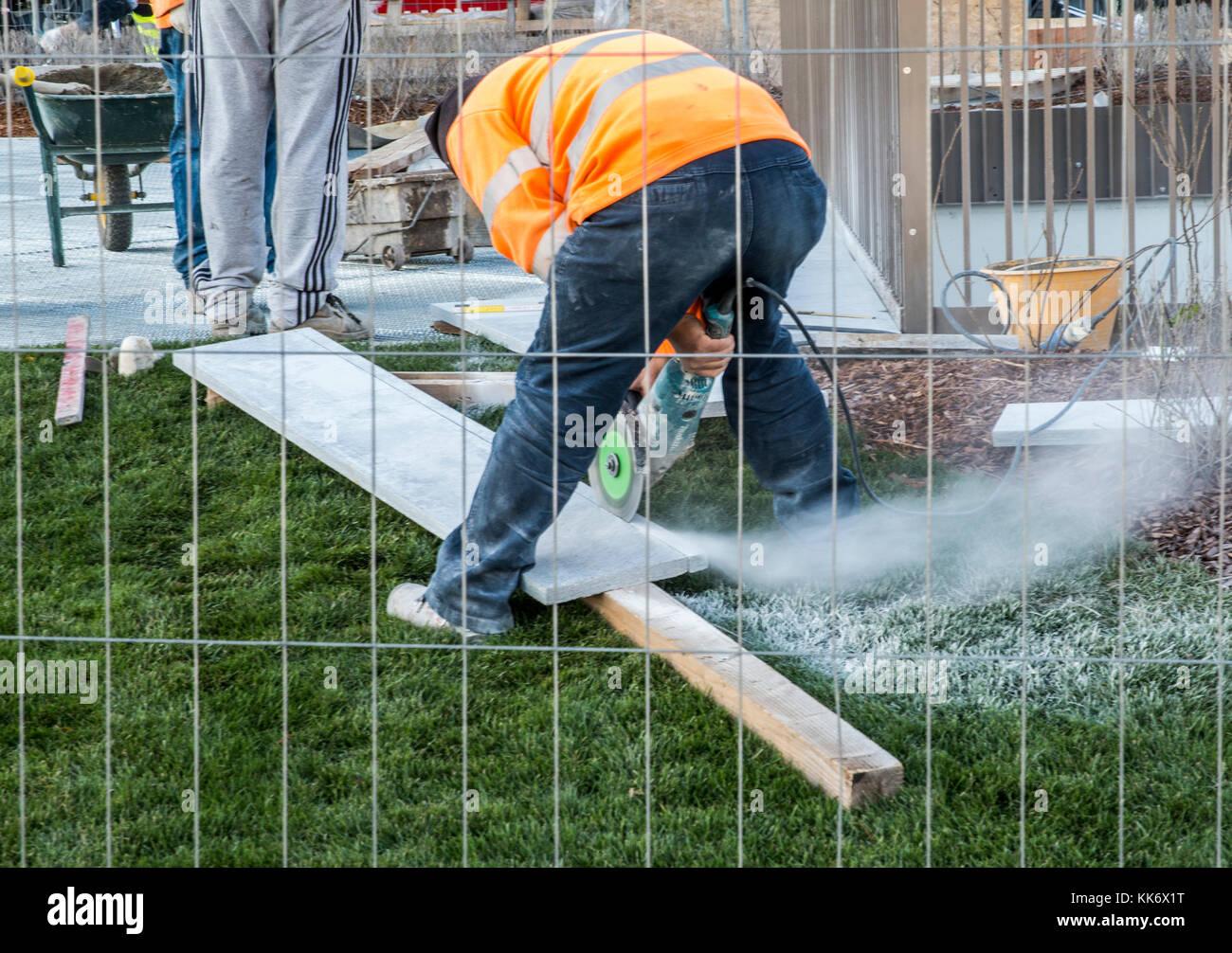Lavoratore in alta visibilità giacca listone di segatura di legno con sega circolare dietro il recinto, tre Immagini Stock
