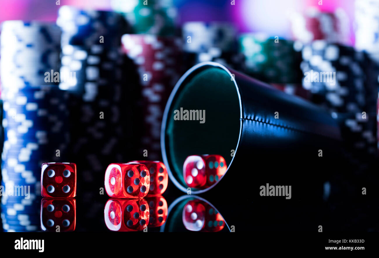 Casino tema. Alto contrasto immagine del casino roulette, poker, gioco di dadi, Poker chips su un tavolo da gioco, tutti su colorato sfondo bokeh di fondo. Foto Stock