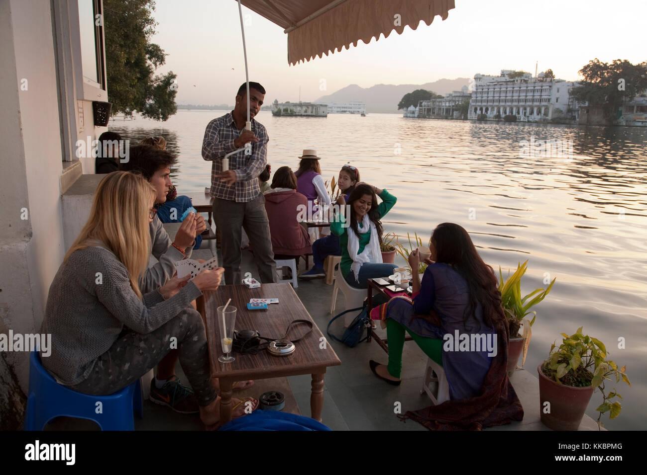 I clienti seduti sulla terrazza sul lago a Jheel Zenzero del Coffee Bar & Bakery, da Chandpol, Udaipur, Rajasthan, India Foto Stock