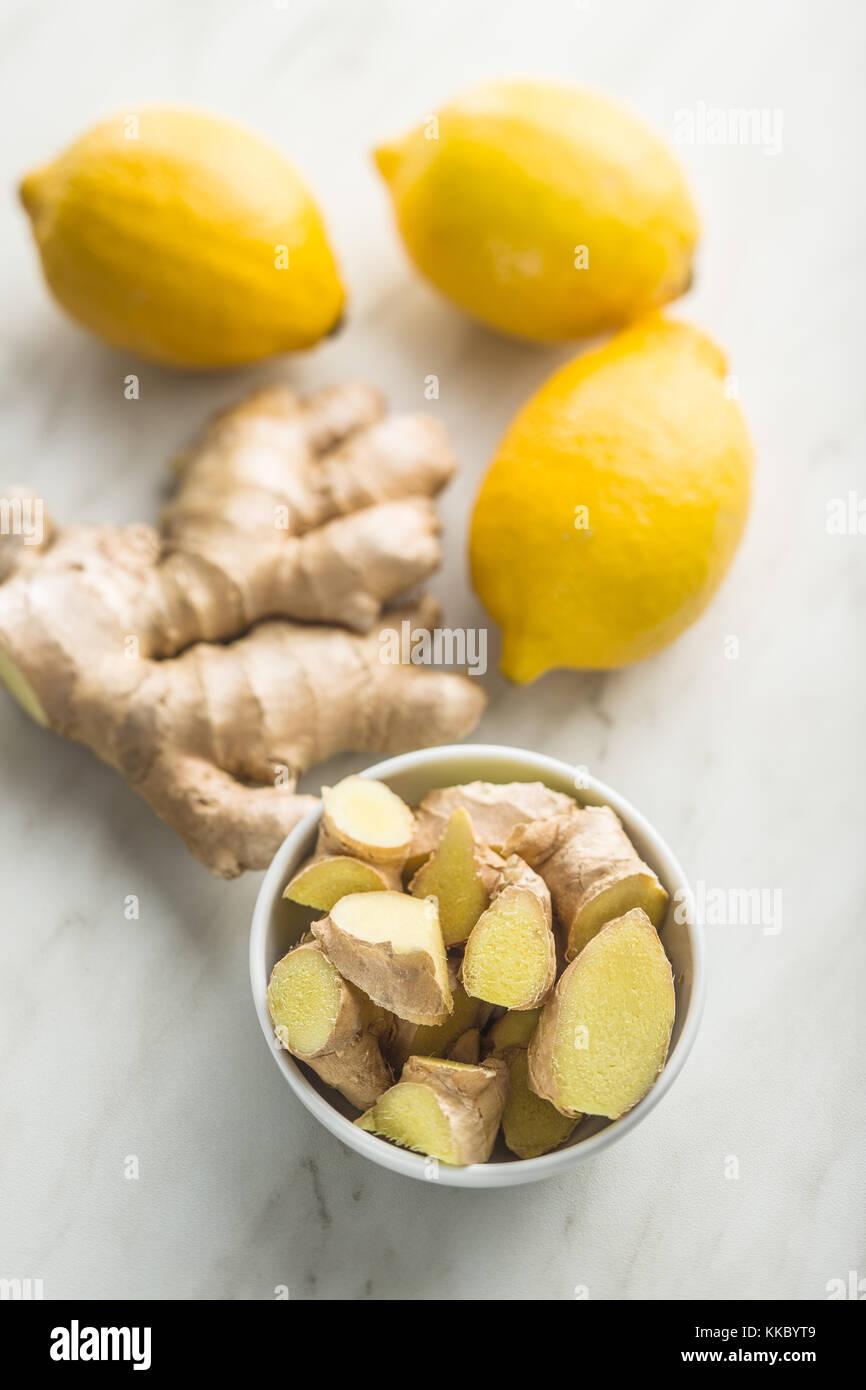 Fette di radice di zenzero e limone giallo. Immagini Stock