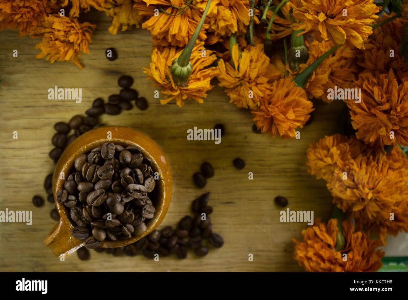 Vista dall'alto di chicchi di caffè all'interno di un messicano fatto a mano tazza circondato da fiori Immagini Stock