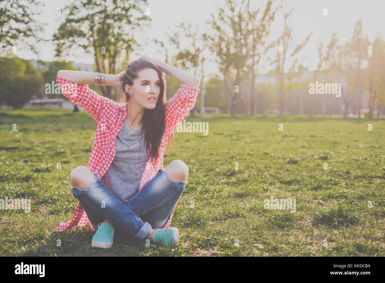 Carino hipster ragazza seduta sul prato verde Immagini Stock