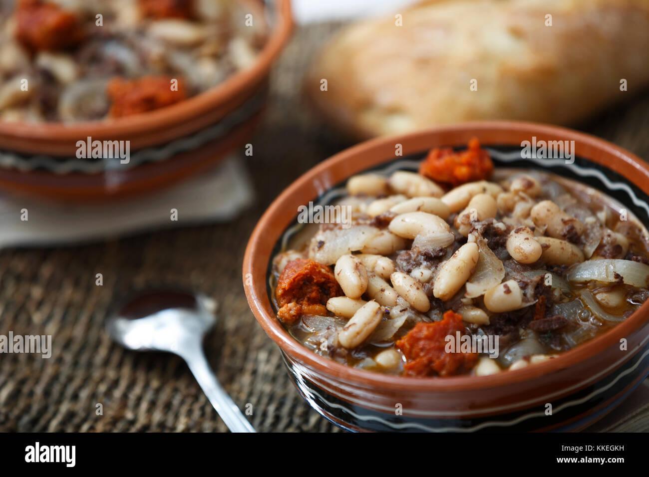 Stufato di fagioli bianchi con salsiccia piccante e pane. Immagini Stock