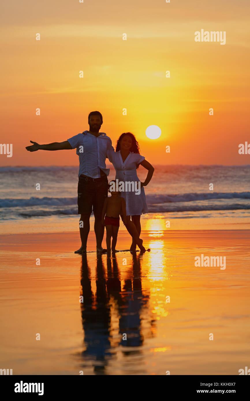 Felice famiglia completa - giovane padre, madre, figlio bambino divertirsi insieme sulla spiaggia di sabbia con mare navigare sul Cielo di tramonto con sun sullo sfondo. Lo stile di vita di viaggio Foto Stock