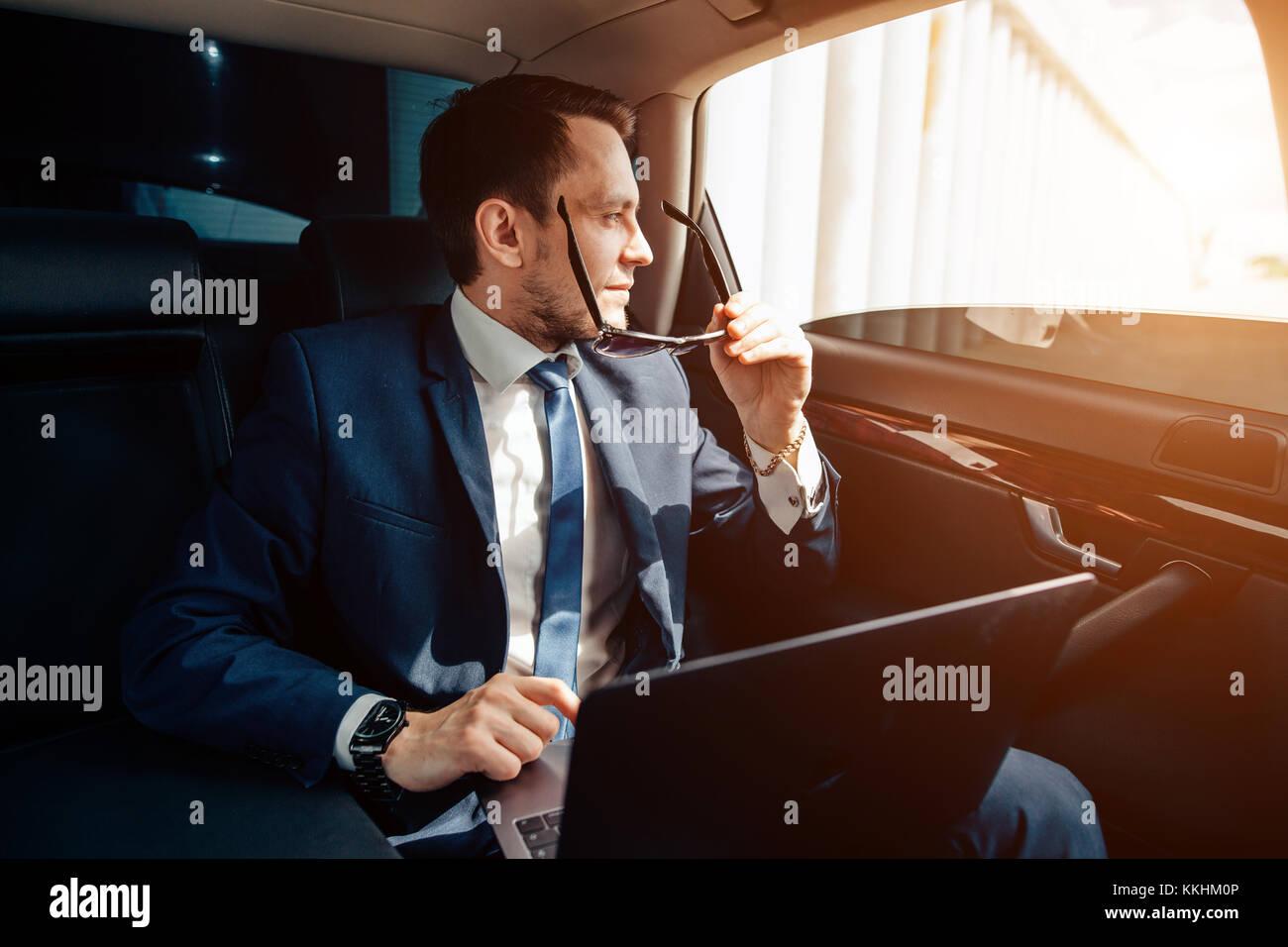 Giovane imprenditore elegante in occhiali da sole sul sedile posteriore della macchina Immagini Stock