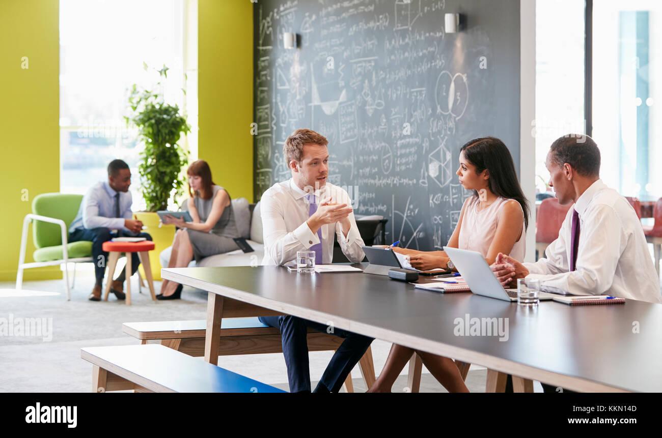 I colleghi di parlare al lavoro in un incontro informale area Immagini Stock