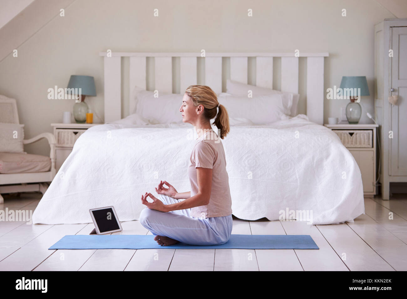 Donna con tavoletta digitale utilizzando la meditazione di app in camera da letto Immagini Stock