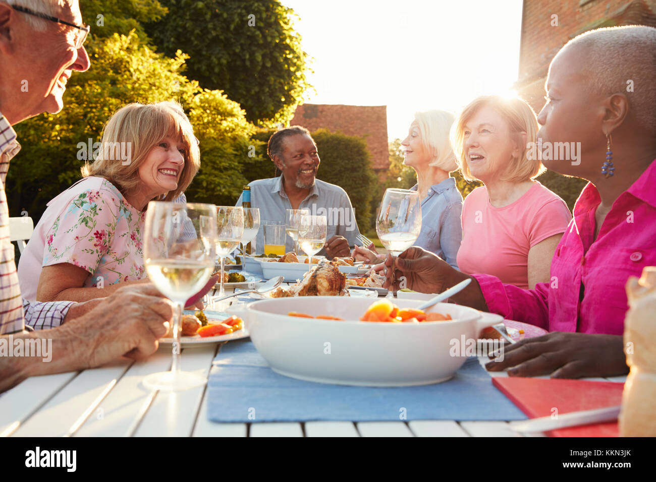 Gruppo di alti amici gustando una cena all'aperto parte a casa Immagini Stock