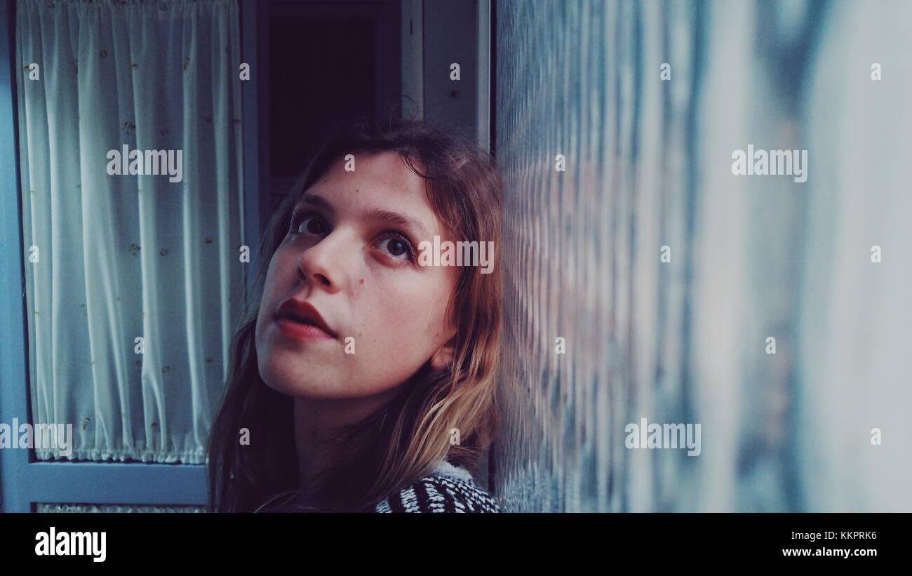 Giovane donna in casa di fronte a una finestra Immagini Stock