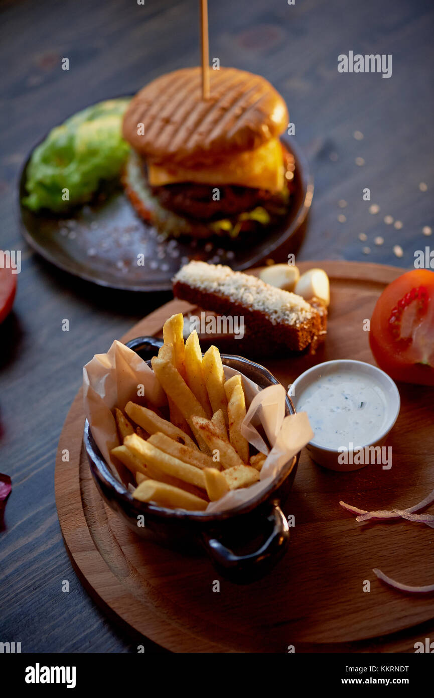 Parte superiore in legno sul suo patatine e hamburger.il concetto del pub e fast food Immagini Stock