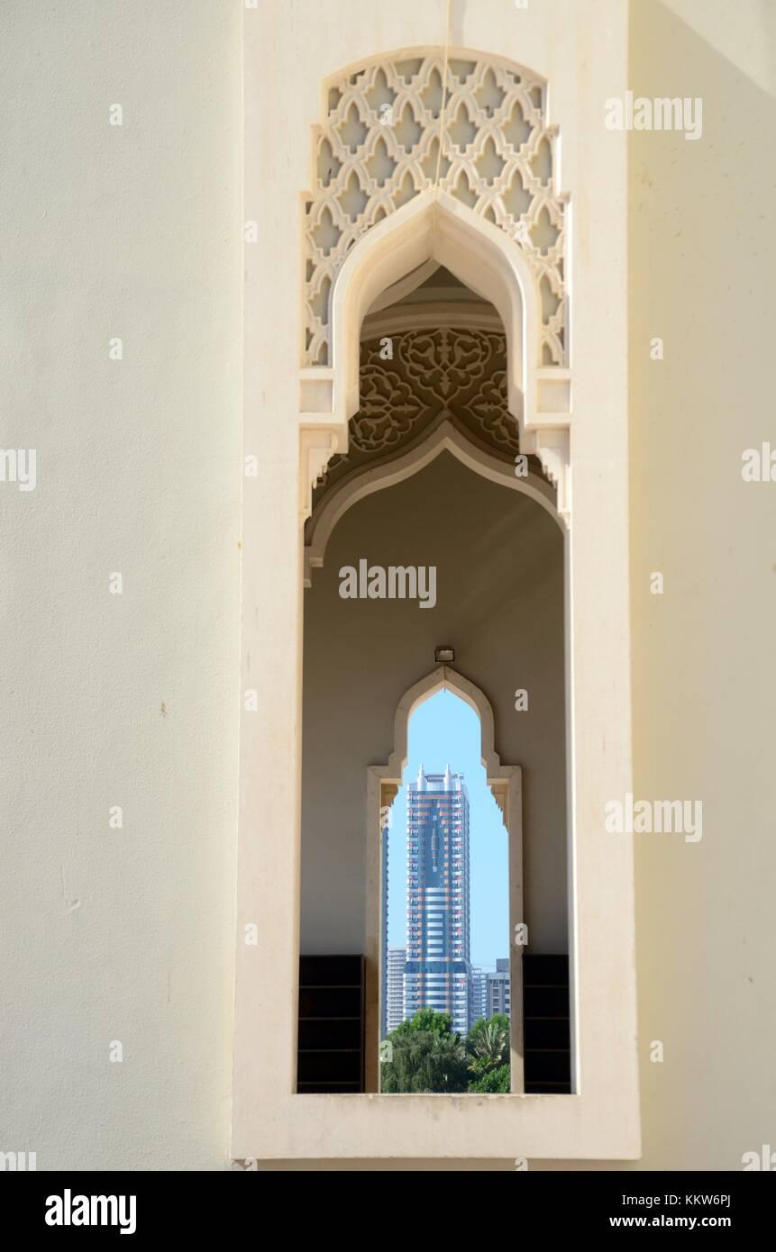 Il contrasto tra il tradizionale e moderna architettura islamica, che mostra una torre alta attraverso la finestra Immagini Stock
