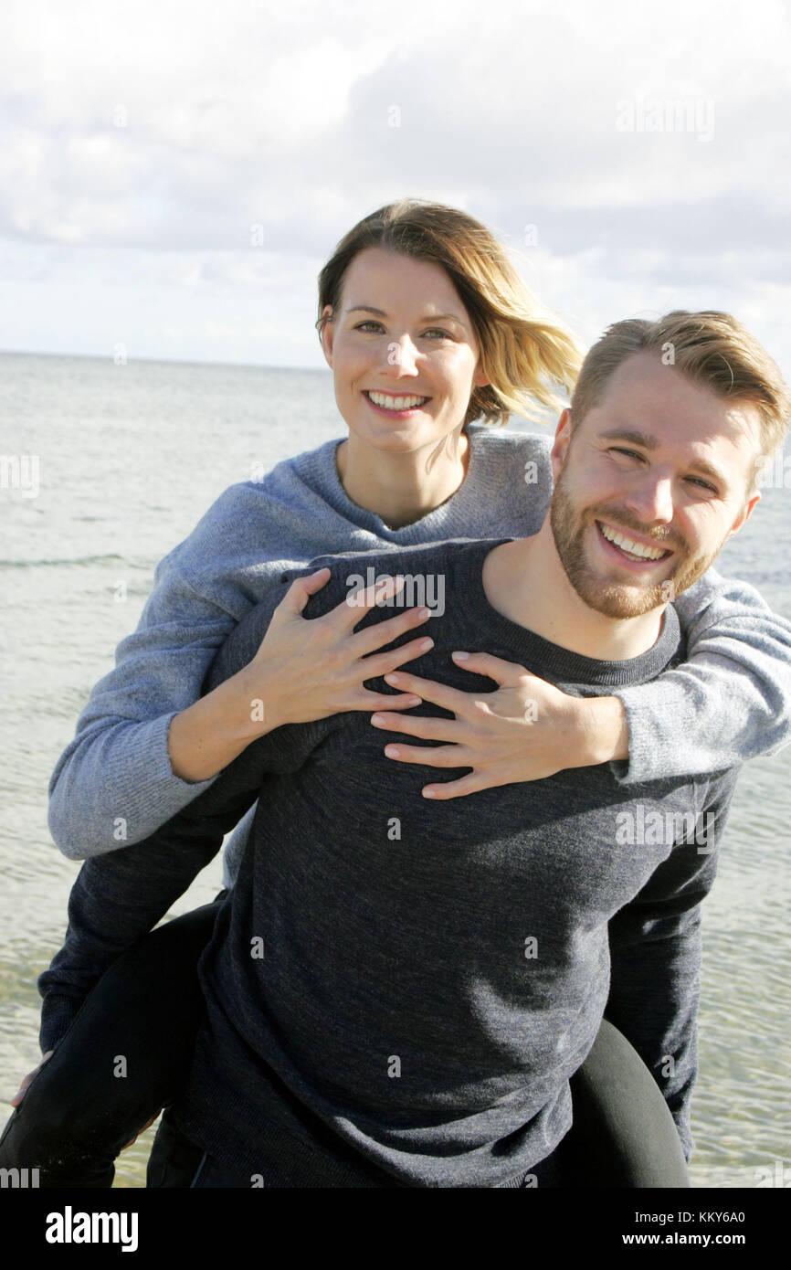 Giovane, mar baltico beach, a piedi, piggyback, Immagini Stock