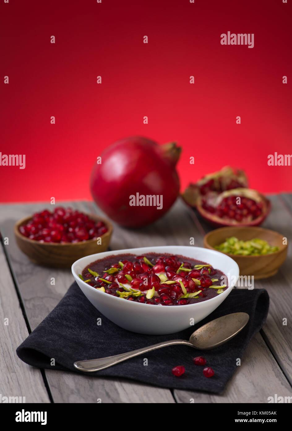 Deserto di melograno con pistacchi, Chia seme, budino di tapioca e yogurt. Il mangiare sano. rosso spazio copia. Immagini Stock