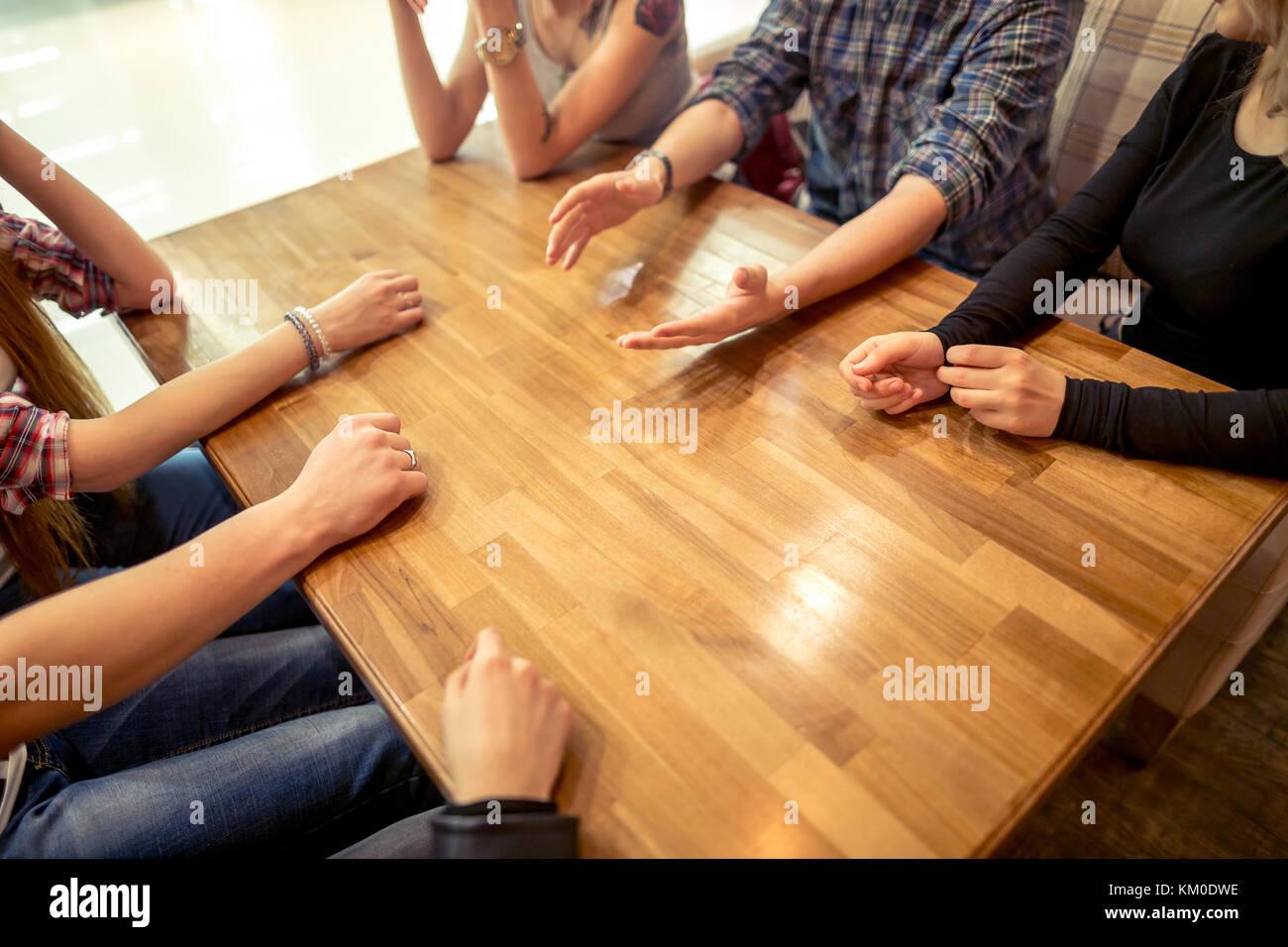 Gruppo di studenti seduti in un caffè bar guardando ogni altro Immagini Stock