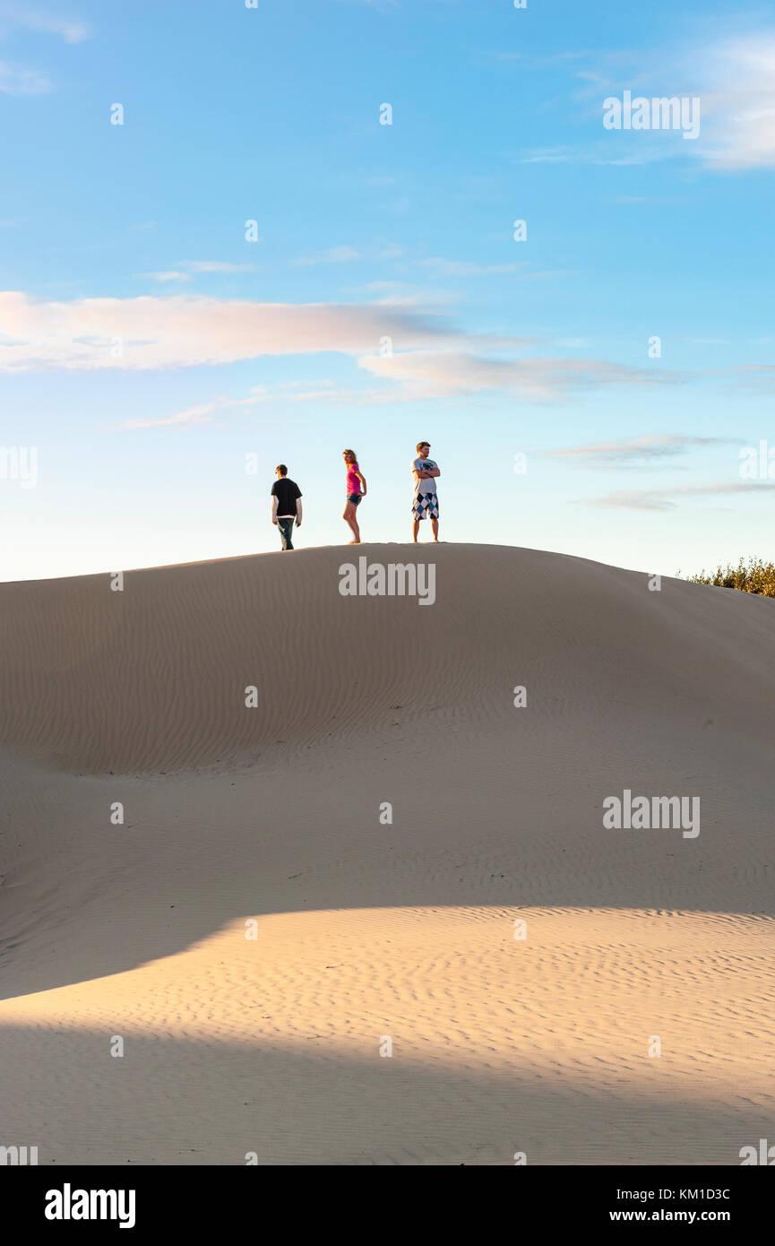 Tre adolescenti camminando sul bordo di dune di sabbia in Oceano Dunes State Vehicular Recreation Area, Oceano dune Immagini Stock