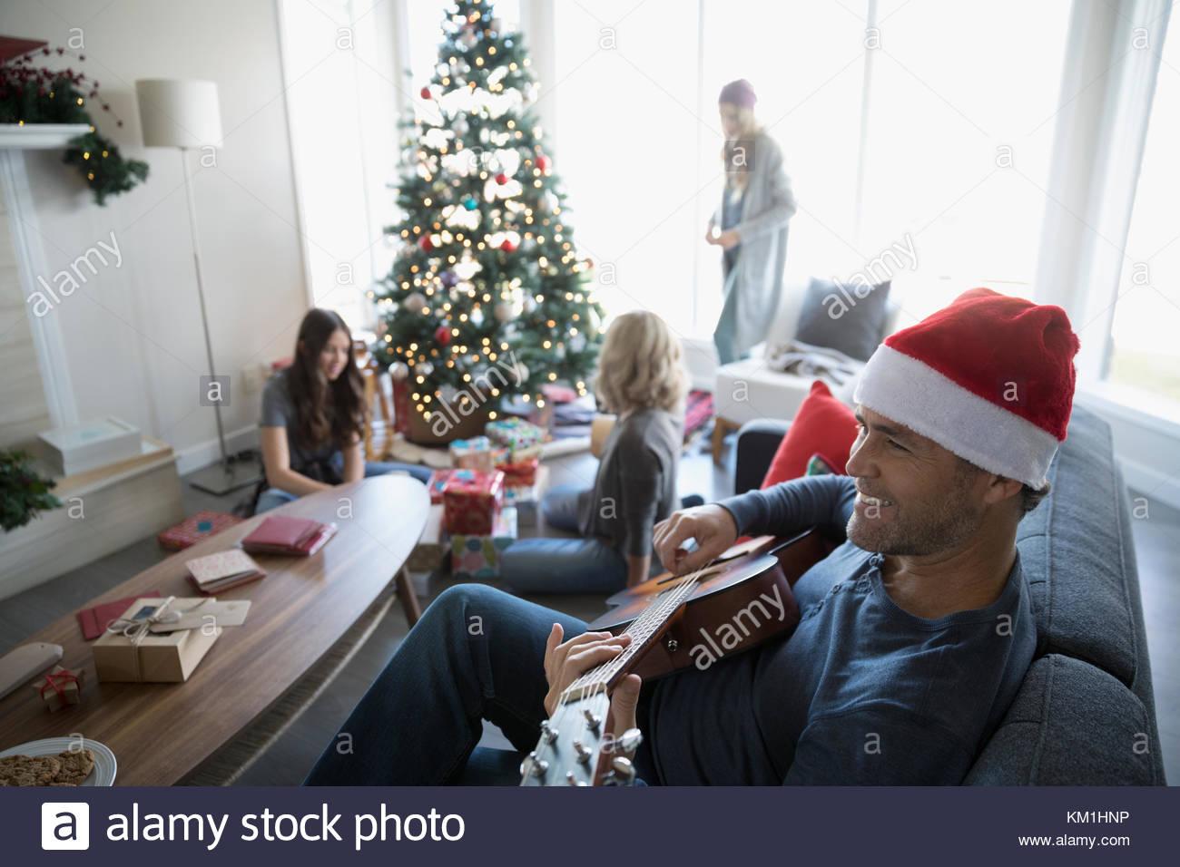 Padre sorridente in Santa hat a suonare la chitarra mentre la famiglia esegue il wrapping di doni in soggiorno con Immagini Stock