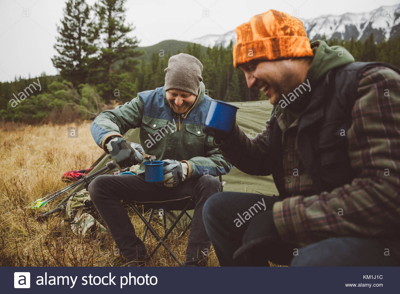 Sorridente cacciatore maschio amici di bere il caffè al di fuori di tenda al campeggio nel campo remoto Immagini Stock