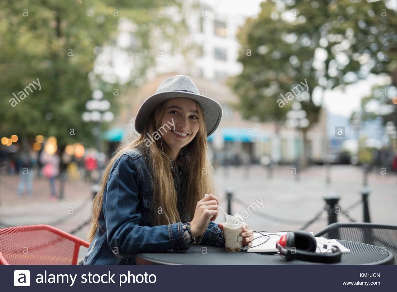 Ritratto sorridente giovane donna a mangiare il gelato a livello urbano sidewalk cafe Immagini Stock