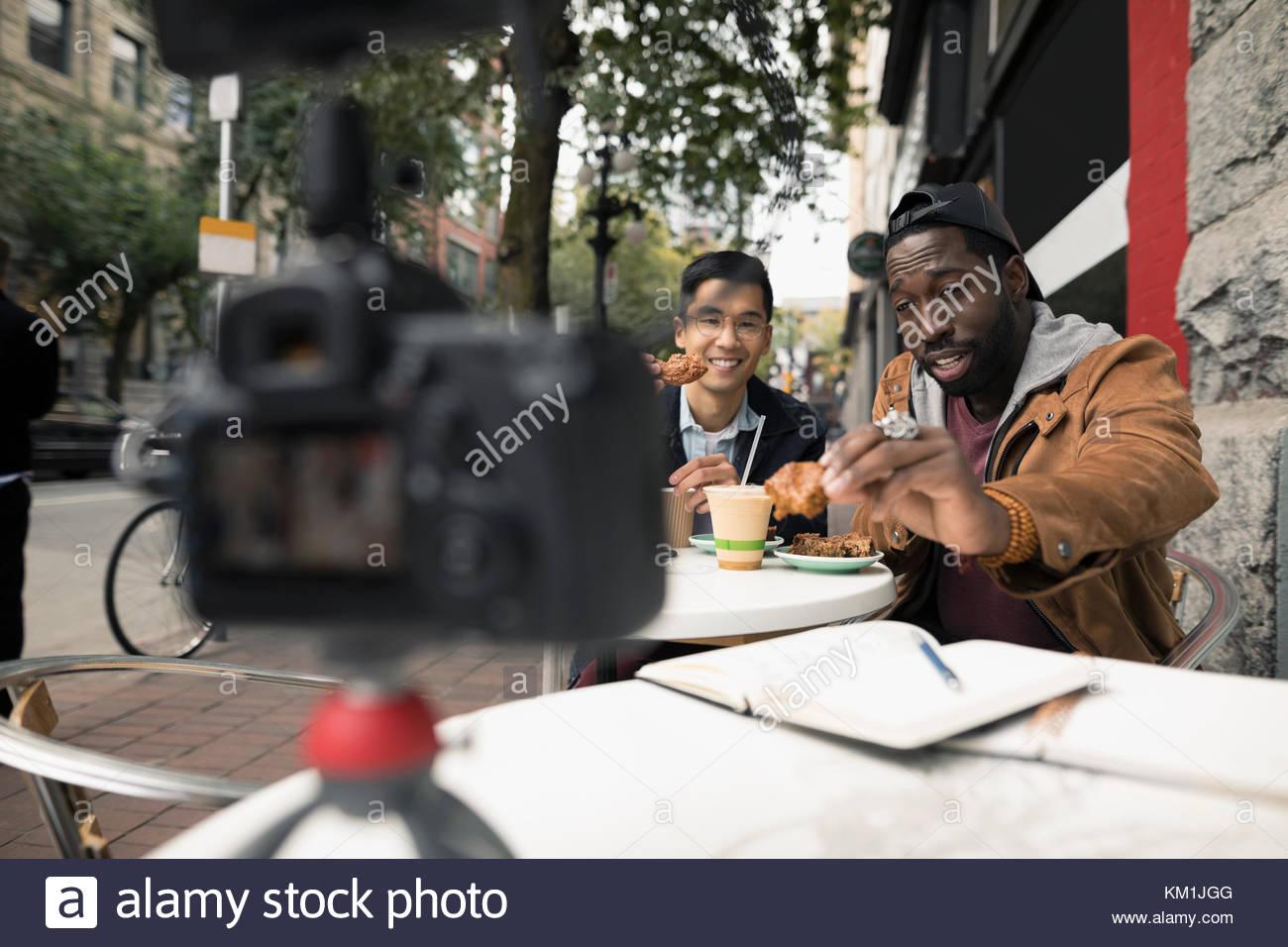 Gli uomini vlogging con videocamera, mangiare a urban cafè sul marciapiede Immagini Stock