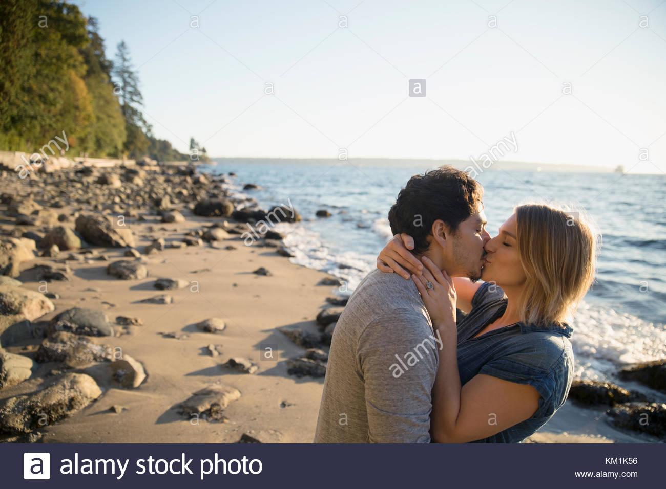 Affettuosa giovane baciare sulla soleggiata spiaggia oceano Immagini Stock