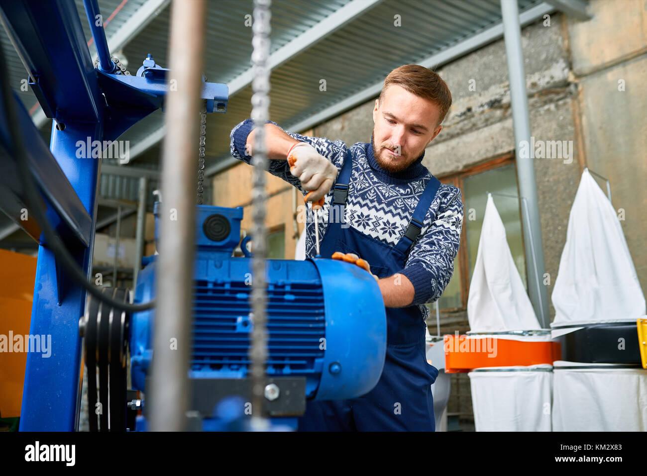 Uomo che ripara unità della macchina presso la fabbrica Immagini Stock
