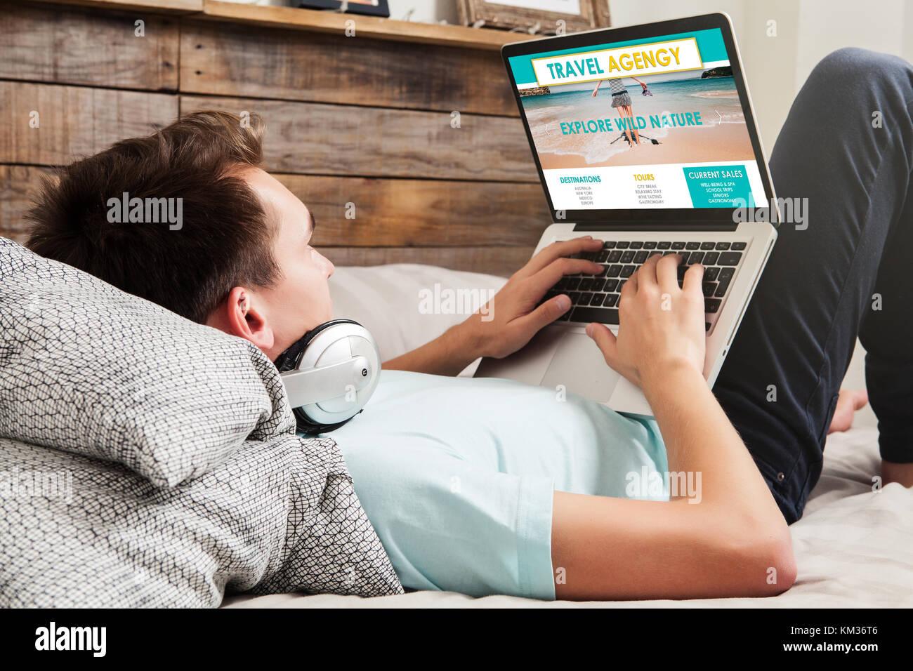 L'Uomo sdraiato sul letto a casa mentre si utilizza un computer portatile per la ricerca di destinazioni di Immagini Stock