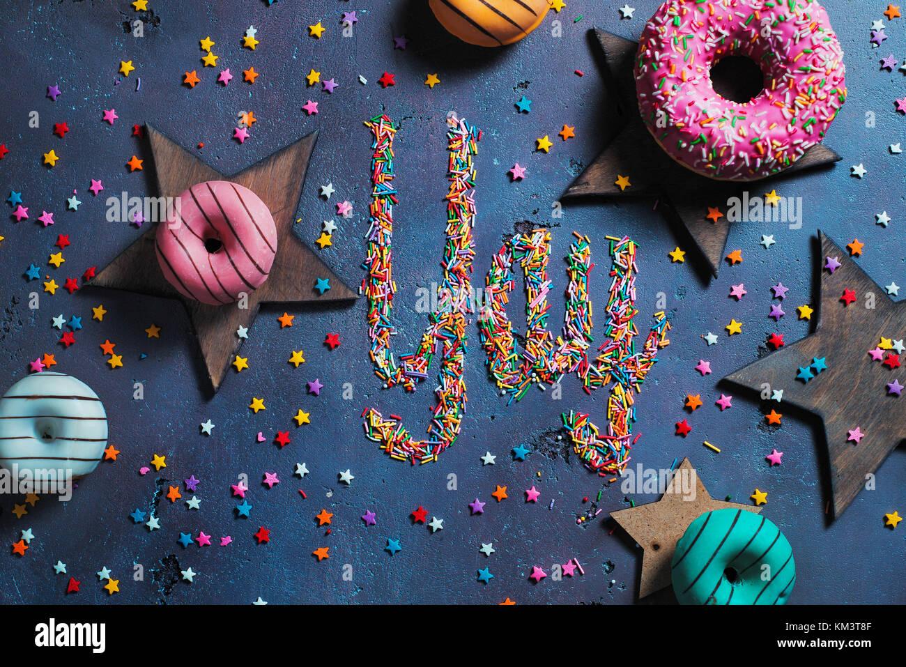 Esclamazione Yay scritto con spruzza su una pietra sfondo con ciambelle e stelle. Parte il concetto di preparazione. Immagini Stock