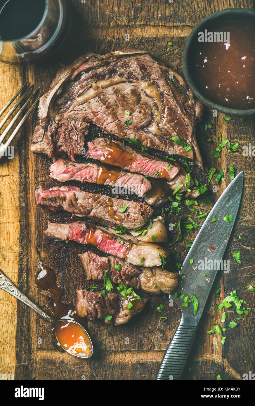 Flat-lay di grigliate di mezzo raro bistecca bistecca di manzo tagliata a pezzi in legno rustico scheda con chutney Immagini Stock