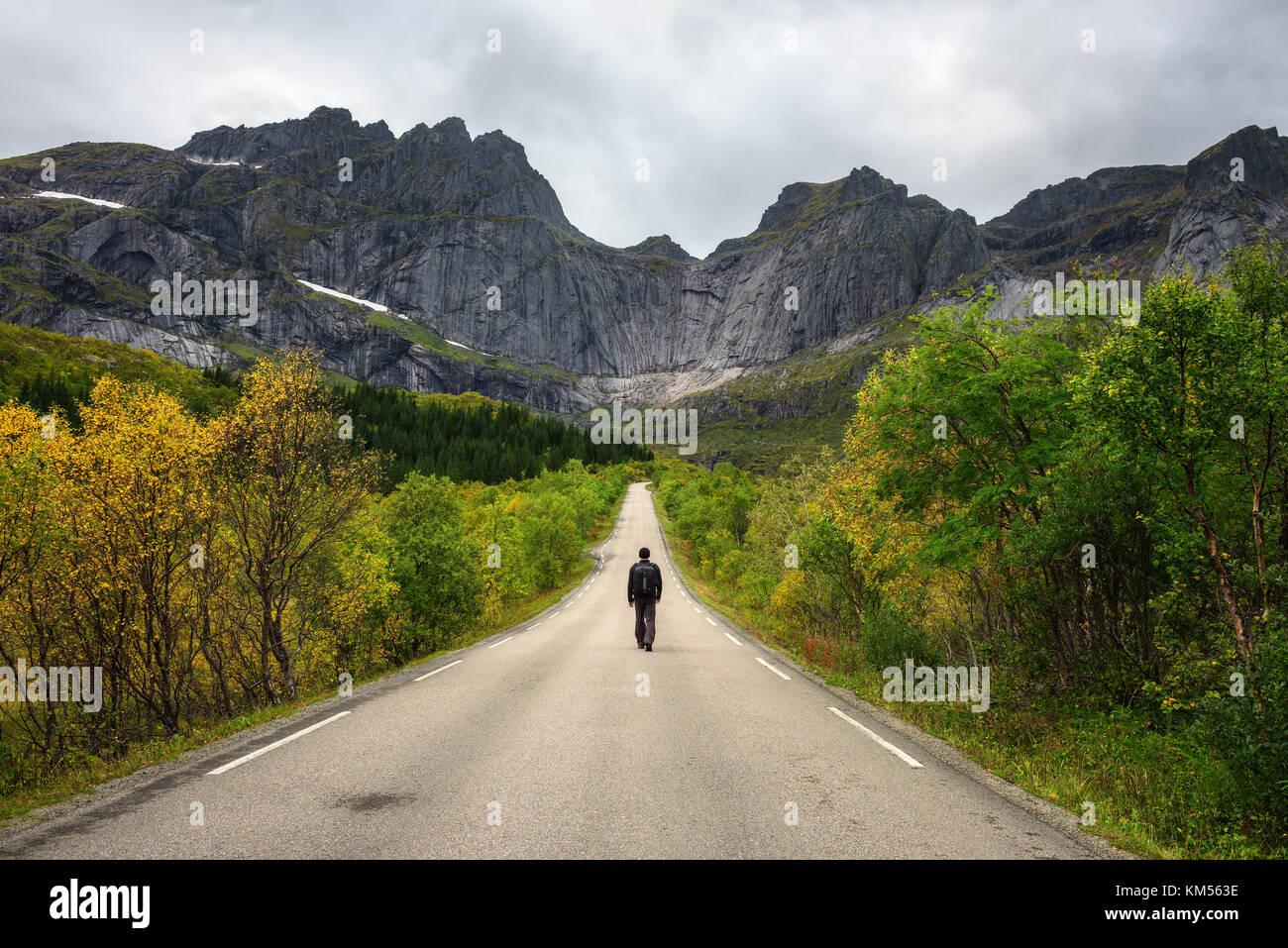 Escursionista cammina su una strada panoramica sulle isole Lofoten in Norvegia Immagini Stock