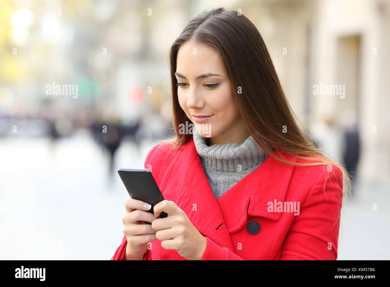 Grave donna utilizzando uno smart phone permanente sulla strada in inverno Immagini Stock