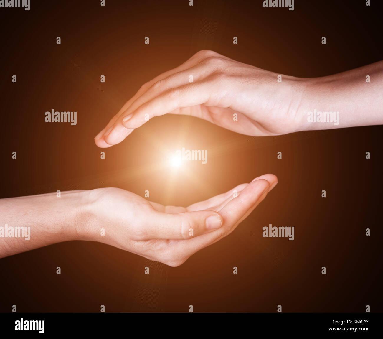 Donna proteggere mani e contenente luminose, incandescente, radiosa, luce splendente. raggi in fasci o espansione Immagini Stock