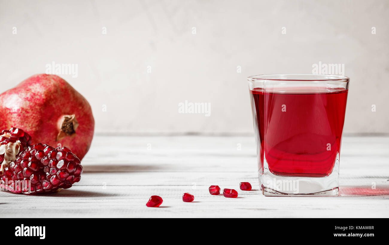 Un bicchiere di succo di melograno con fresca frutta melograno e semi sparsi sul tavolo di legno. bibita salutare Immagini Stock