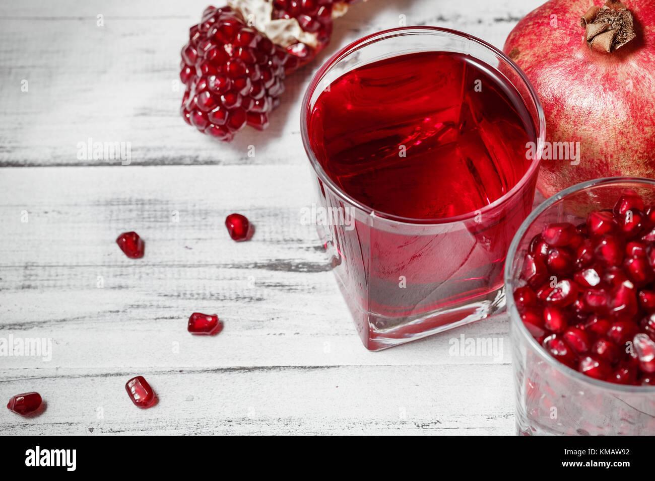 Bicchiere di succo di melograno e un altro riempito con semi con fresca frutta melograno e semi sparsi sul tavolo Immagini Stock
