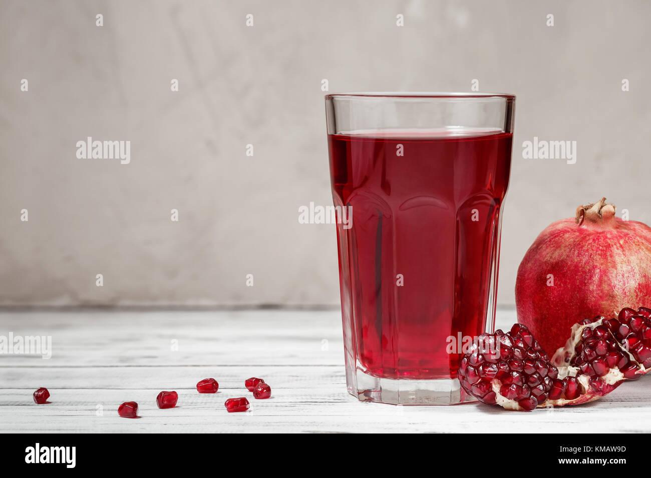 Un bicchiere di succo di melograno wiyh freschi frutti di melograno e semi sparsi sul tavolo di legno con copia Immagini Stock