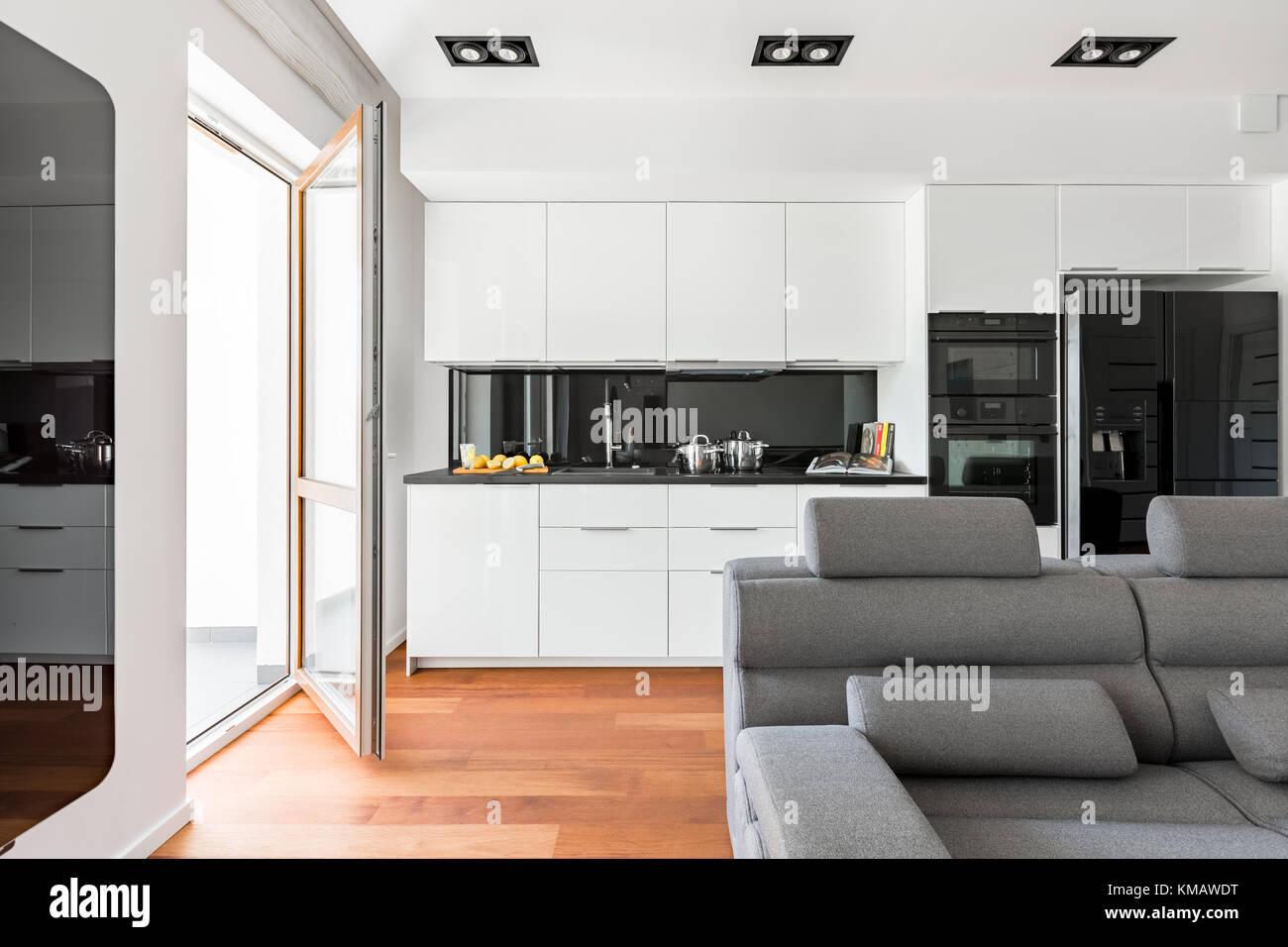 Soggiorno moderno con divano, balcone e bianco, cucina ...