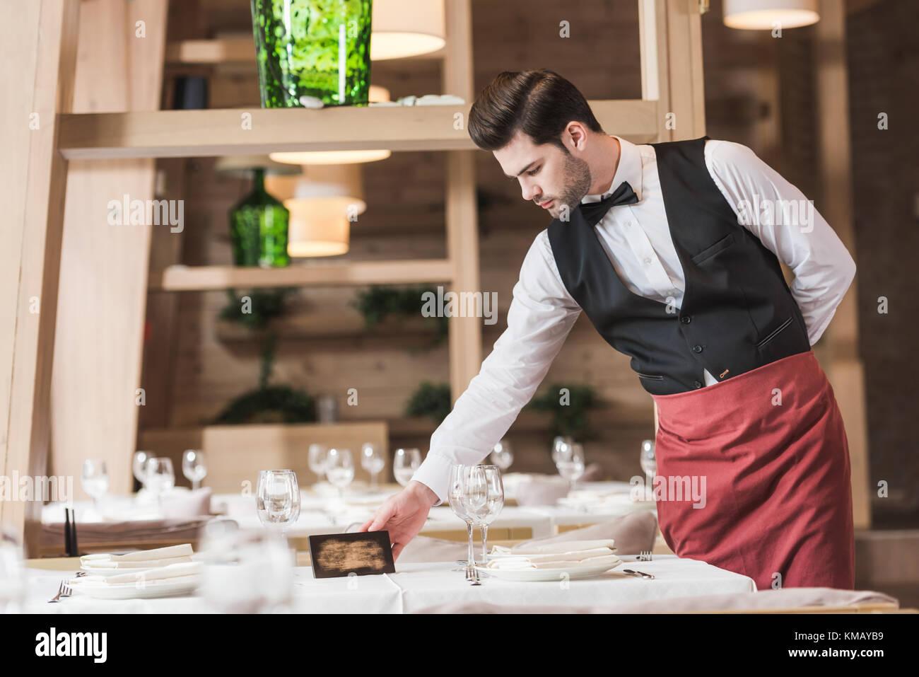 Cameriere mettendo riservati segno Immagini Stock