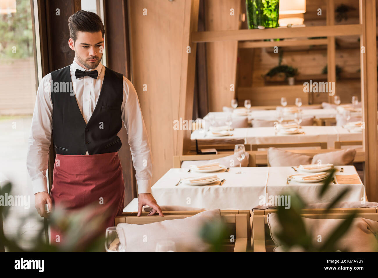 Cameriere guardando servita tabella Immagini Stock