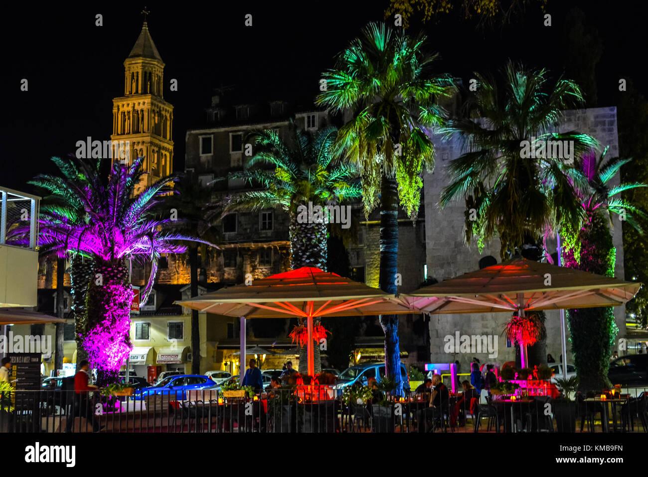 Un Colorato Caf Sul Marciapiede Sulla Riva Passeggiata Lungomare Spalato Croazia A Tarda Notte Con Palme Ombrelli E Torre Illuminato Luci