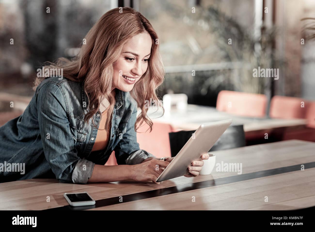 Positivo giovane donna guardando il suo moderno tablet e sorridente Immagini Stock