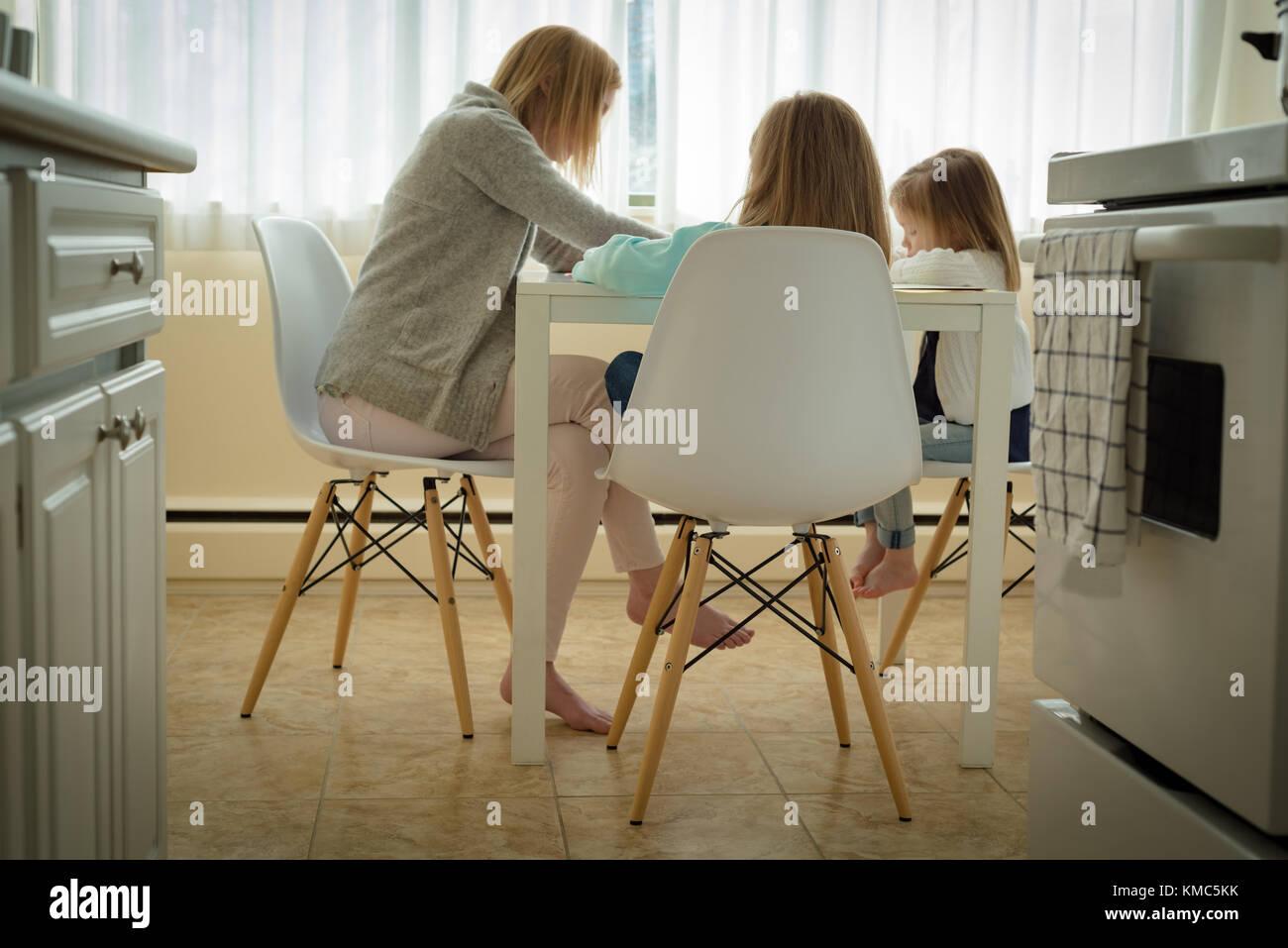 Madre aiutando i suoi figli in studi Immagini Stock