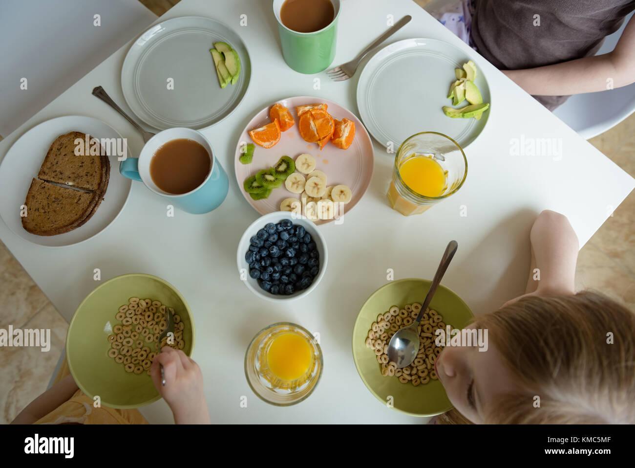 Madre e bambini con prima colazione Immagini Stock