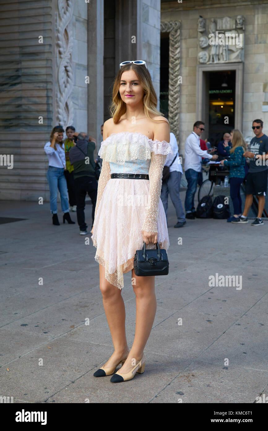 Milano - 23 settembre  donna con luce rosa e vestito blu e nero borsa  versace davanti a Gabriele colangelo fashion show cc4f381193de