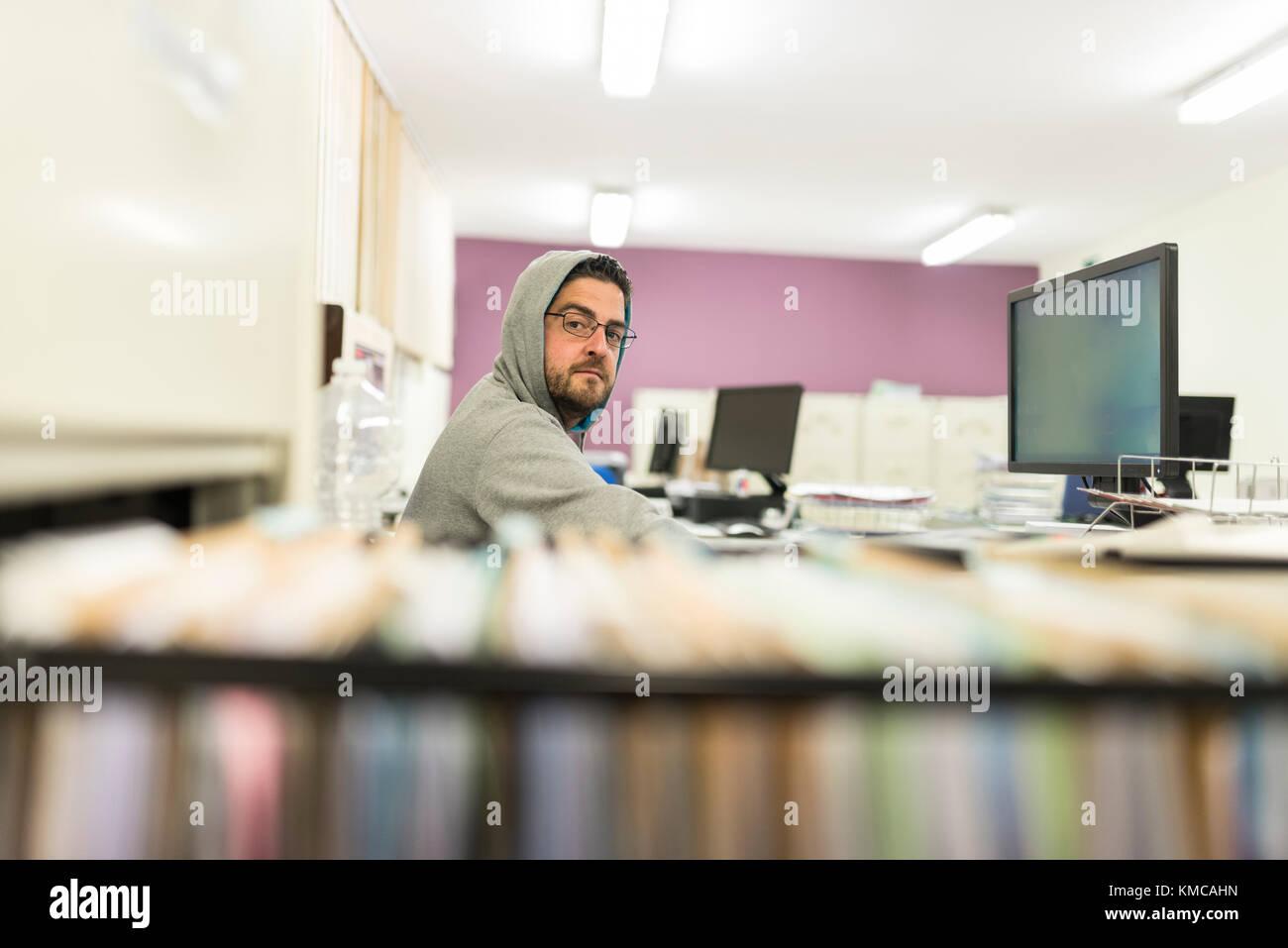 40 anni di vecchio uomo cerca computer e lavorare con felpa e cappa in office Immagini Stock